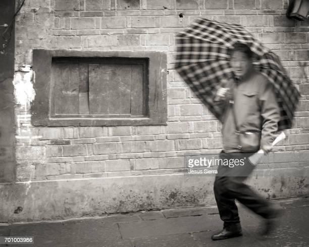 Man with umbrella walking, Fenghuang, Hunan Province, China, Asia