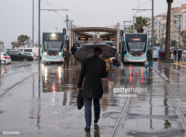 man with umbrella walking to catch the cable car. - emreturanphoto stock pictures, royalty-free photos & images