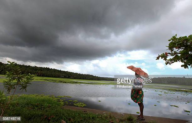 A man with umbrella watch dark clouds gathering over a lagoon as the first winds of southwest monsoon hits Kerala on June 7 2016 in...