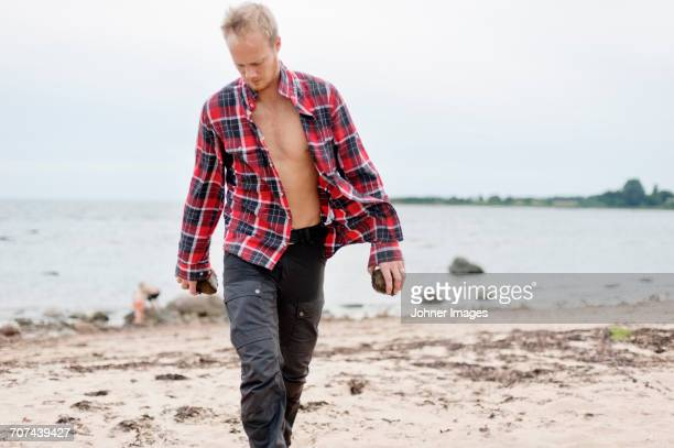 Man with unbuttoned shirt walking on beach