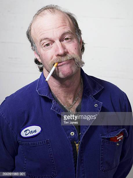 Man with unlit cigarette dangling from mouth, portrait