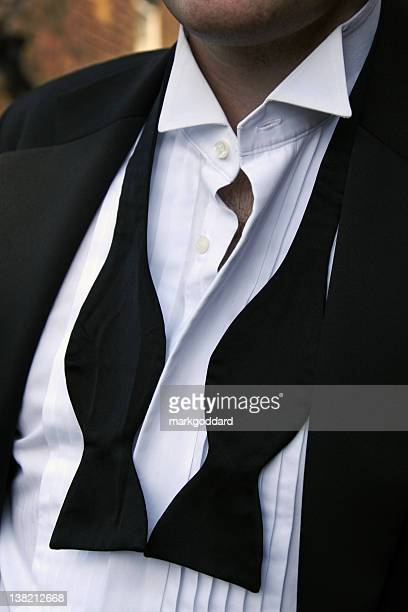 Man with untied black bowtie and unbuttoned white shirt