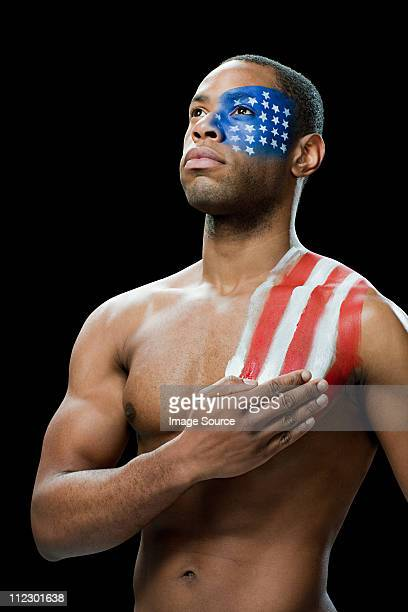 Man with US flag painted on face and shoulder, hand on chest
