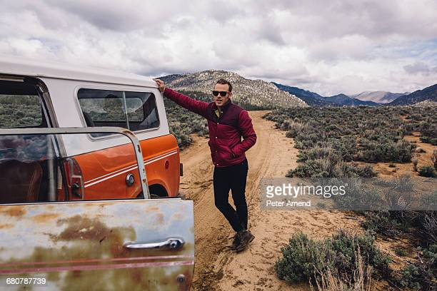 Man with vehicle on scrubland by mountains, Kennedy Meadows, California, USA