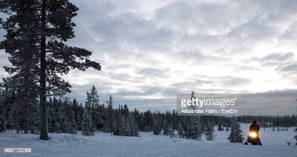 man with vehicle on snowfield against sky during sunset - snowfield stock pictures, royalty-free photos & images