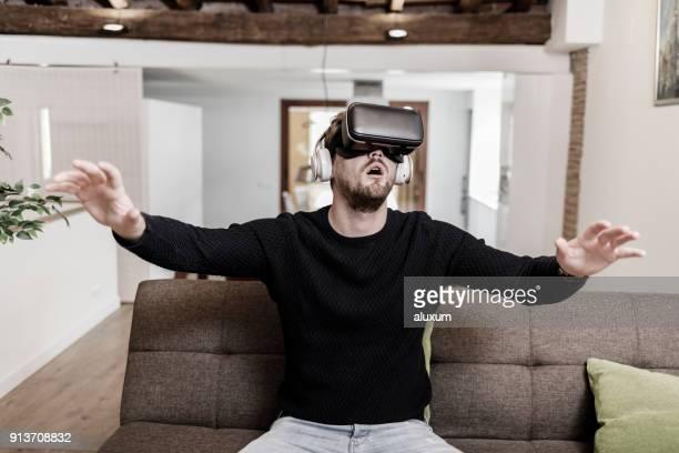 Hombre con gafas de realidad virtual en casa