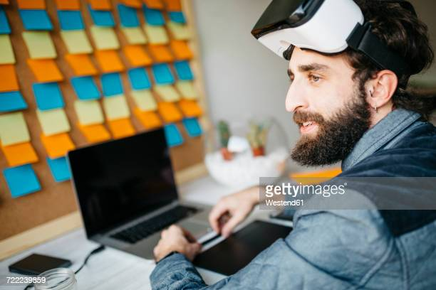 Man with Virtual Reality Glasses working on new project in his office