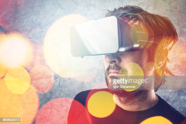 Man with virtual reality goggles watching 3d VR multimedia conte