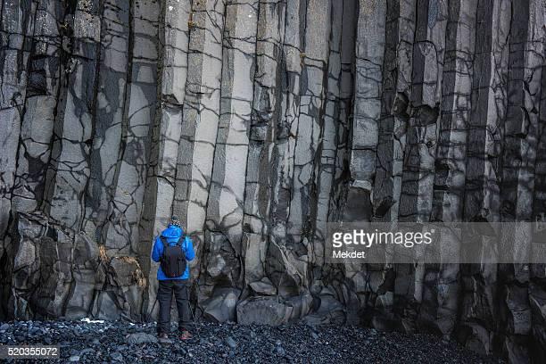 A man with volcanic Basalt cliff at Reynisfjara, Iceland