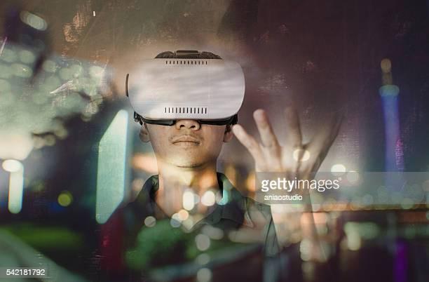 Mann mit VR-headset mit Geste und die Stadt bei Nacht