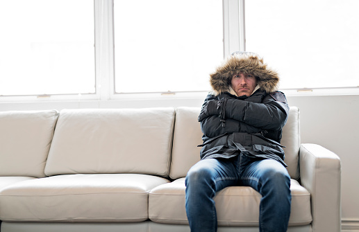 Man With Warm Clothing Feeling The Cold Inside House on the sofa 903058308