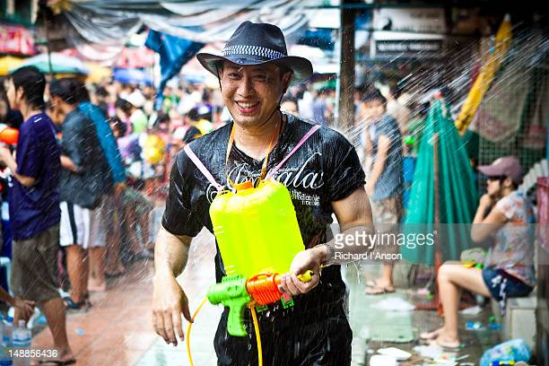 Man with water pistol on Khaosan Road at Thai New Year Songkran Festival.