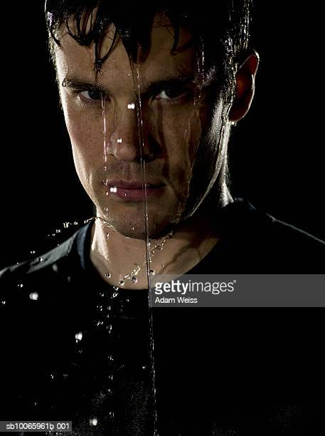 Man with water running down face, close-up, portrait