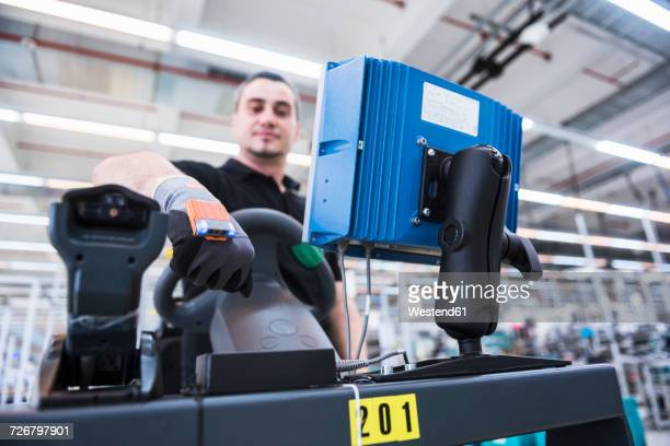 Man with wearable scanner on tugger train in factory shop floor