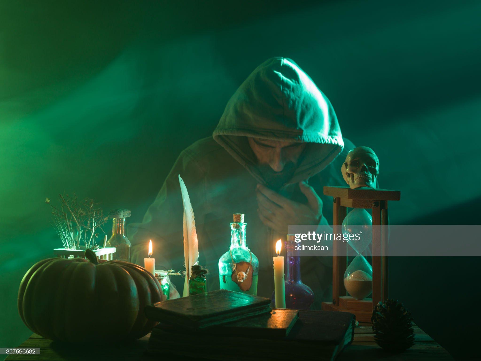 ハロウィーンの魔法を作るフード付きのコートを着て男 : ストックフォト