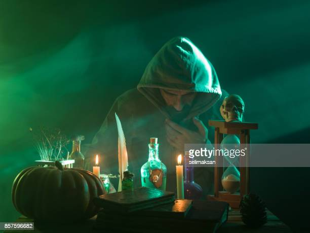 man with wearing a hooded coat making magic for halloween - wizard stock pictures, royalty-free photos & images