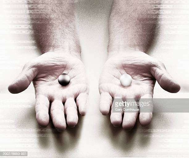 man with white and black balls on palm of hands, close-up - two objects stock pictures, royalty-free photos & images