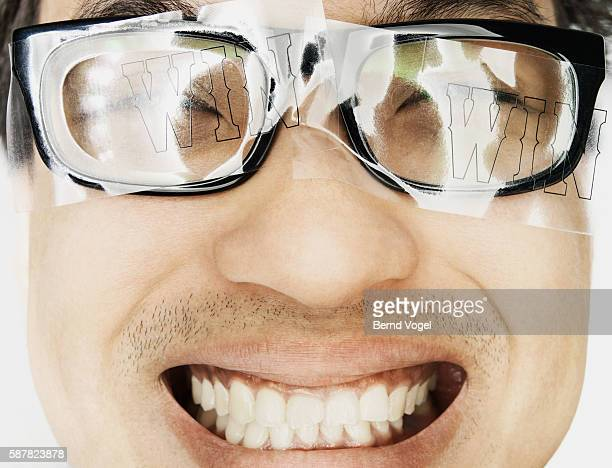 Man with 'win' text on eyeglasses