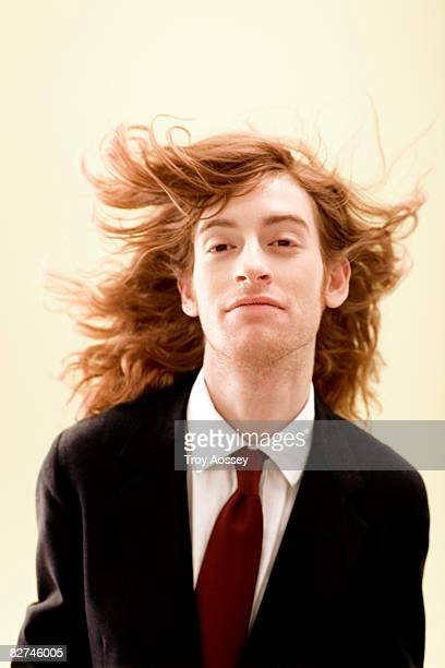 man with wind blown hair in business suit