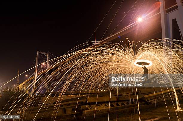Man With Wire Wool At Figueira Da Foz Bridge Against Sky During Night