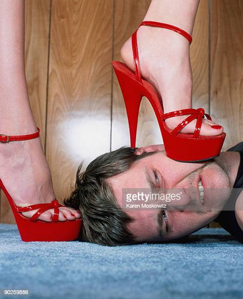 man with woman in high heels stepping on his face - talons aiguilles photos et images de collection