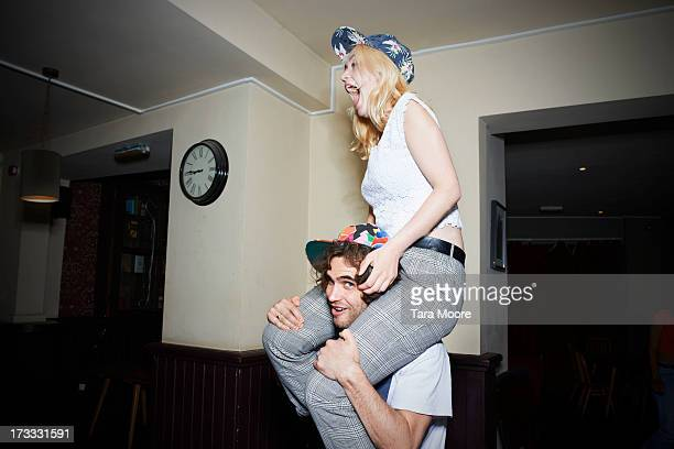 man with woman on shoulders having fun