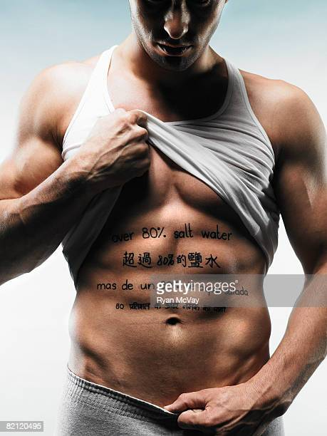 man with words written on stomach - male belly button stock photos and pictures