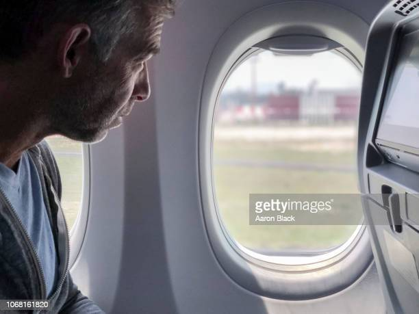 Man with wrinkles looks out the window from his seat on an airplane.