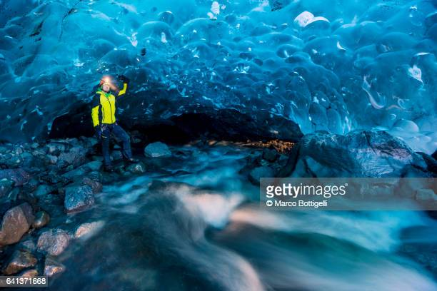 Man with yellow coat by a flowing river inside a crystal ice cave in winter. Iceland.