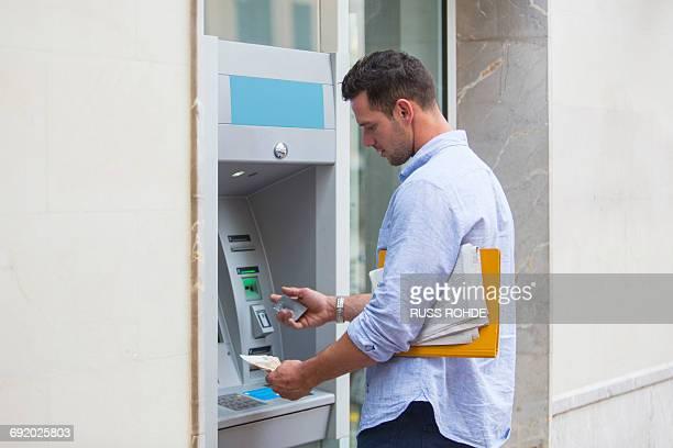 man withdrawing cash from cash machine - geldautomat stock-fotos und bilder