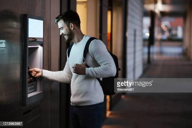 man withdrawing money at an atm in the city - geldautomat stock-fotos und bilder