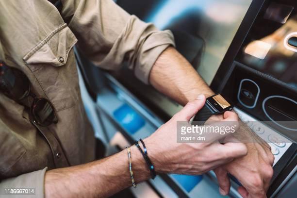 mann zieht mit smartwatch geld ab - kleine uhr stock-fotos und bilder