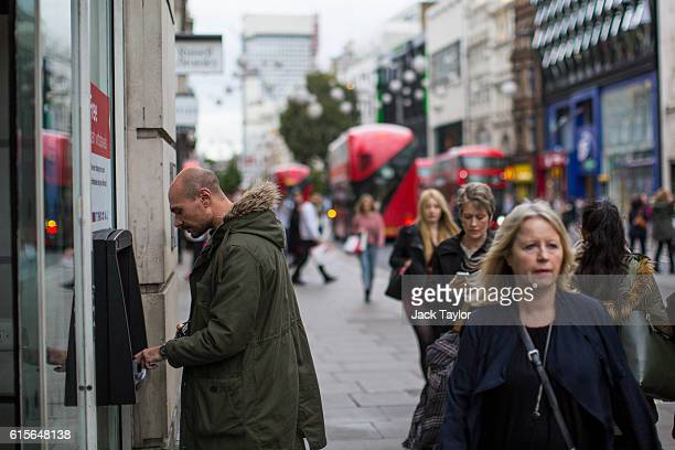 A man withdraws cash from an ATM on Oxford Street on October 19 2016 in London England Inflation rose to 10% in September up from 06% in August...