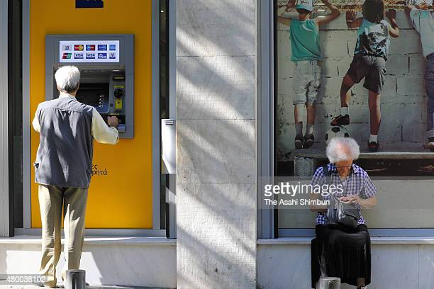 A man withdraws cash from ATM on July 9 2015 in Athens Greece The Greek government has hours left to offer Eurozone creditors a viable plan to...