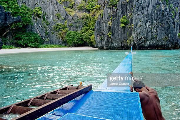 EL NIDO PALAWAN PHILIPPINES A man withdraws his boat to a beach that lies hidden behind rocks