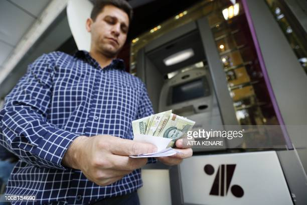 A man withdraws Iranian Rials from an automated teller machine in the capital Tehran on July 31 2018 Iran's currency traded at a fresh recordlow of...