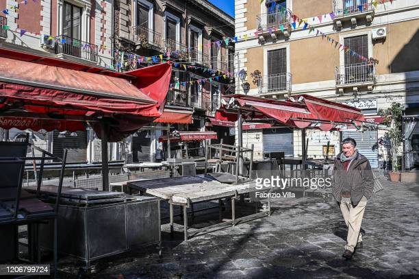 A man without a protective mask crosses the traditional fish market a piscaria closed due to the Coronavirus emergency on March 12 2020 in Catania...