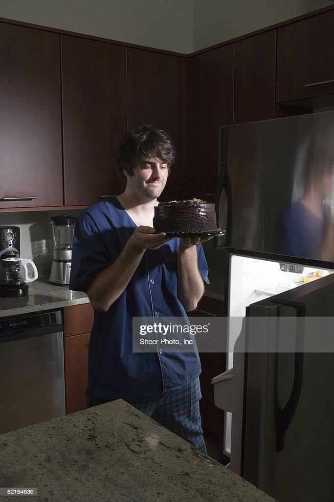 man withrefrigerator holding chocolate cake : Stock Photo