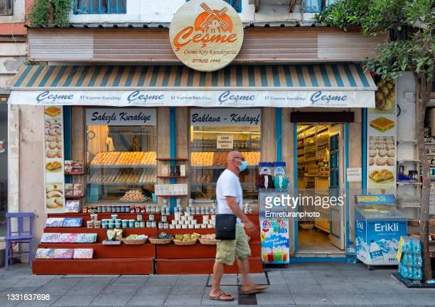 man wlaking in front of a pastry shop in çeşme town in aegean turkey in the summer,2021 - emreturanphoto stock pictures, royalty-free photos & images