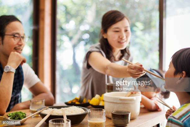 man, woman and boy sitting round a table with bowls of food, eating together. - 両親 ストックフォトと画像