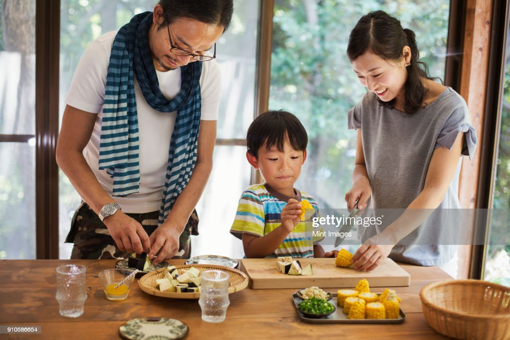 Man, woman and boy standing at a table, preparing corn on the cob, smiling. : Stock Photo