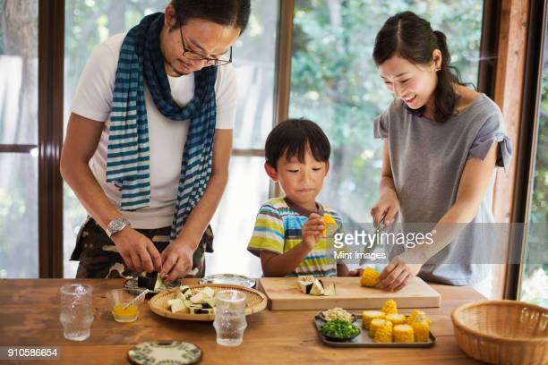 man, woman and boy standing at a table, preparing corn on the cob, smiling. - 夫婦 ストックフォトと画像