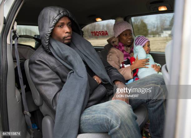 A man woman and their baby all from Haiti wait in a taxi to be taken to the US/Canada border February 27 2017 in Plattsburgh NY The couple travelled...