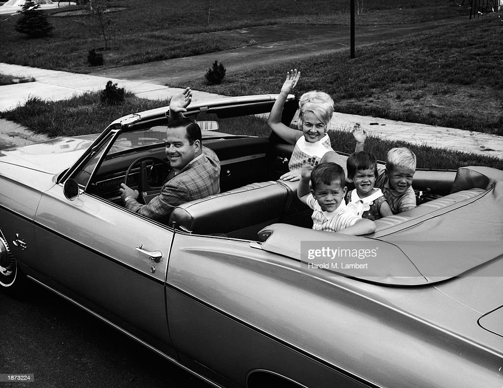 Family Waves From 1960s Convertible. : News Photo