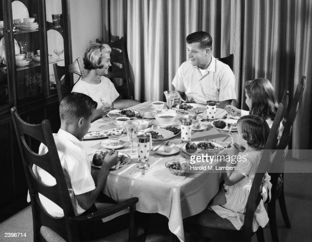 A man woman and three young children eat dinner at a dining room table 1950s