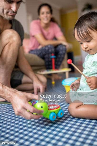 Man, woman and toddler playing in the living room