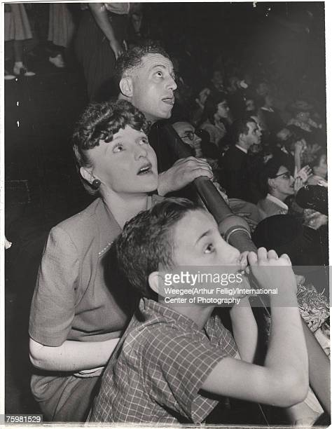 Man, woman, and young boy all look upwards, along with other audience members, at the aerial acts of the Ringling Brothers Contintental Circus, June...