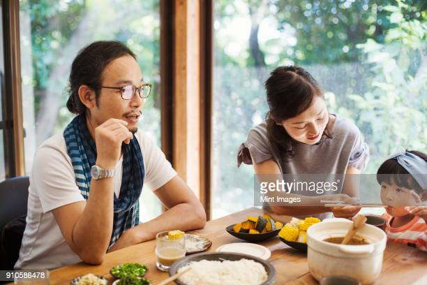man, woman and young girl sitting round a table with bowls of food, eating together. - 夫婦 ストックフォトと画像