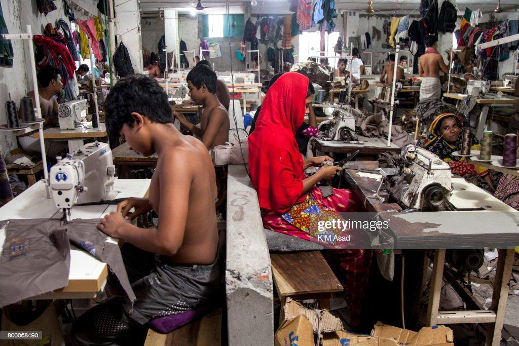 Man, Woman, Children sews a cloth in a local garment shop in... : News Photo