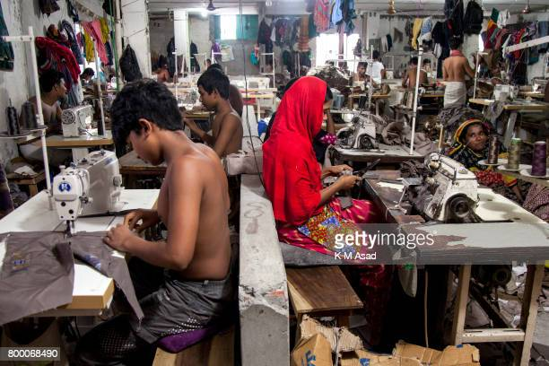 SADARGHAT DHAKA BANGLADESH Man Woman Children sews a cloth in a local garment shop in Dhaka Bangladesh World Day Against Child Labor was observed on...